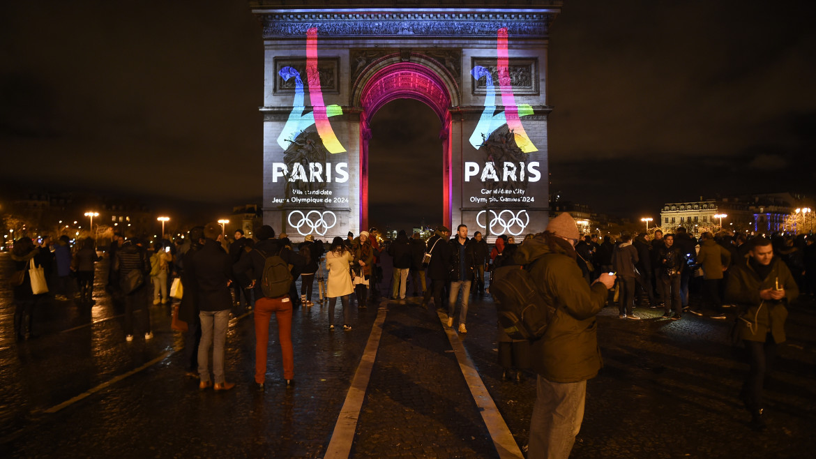 People watch as the campaign's official logo of the Paris bid to host the 2024 Olympic Games is seen on the Arc de Triomphe in Paris on February 9, 2016.  AFP PHOTO / LIONEL BONAVENTURE / AFP / LIONEL BONAVENTURE