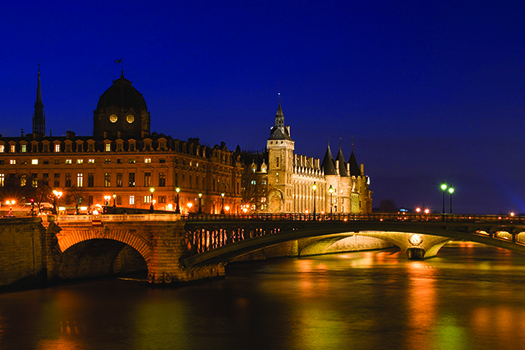 Night view of the Conciergerie (old medieval jailhouse) and the Seine river - Paris, France